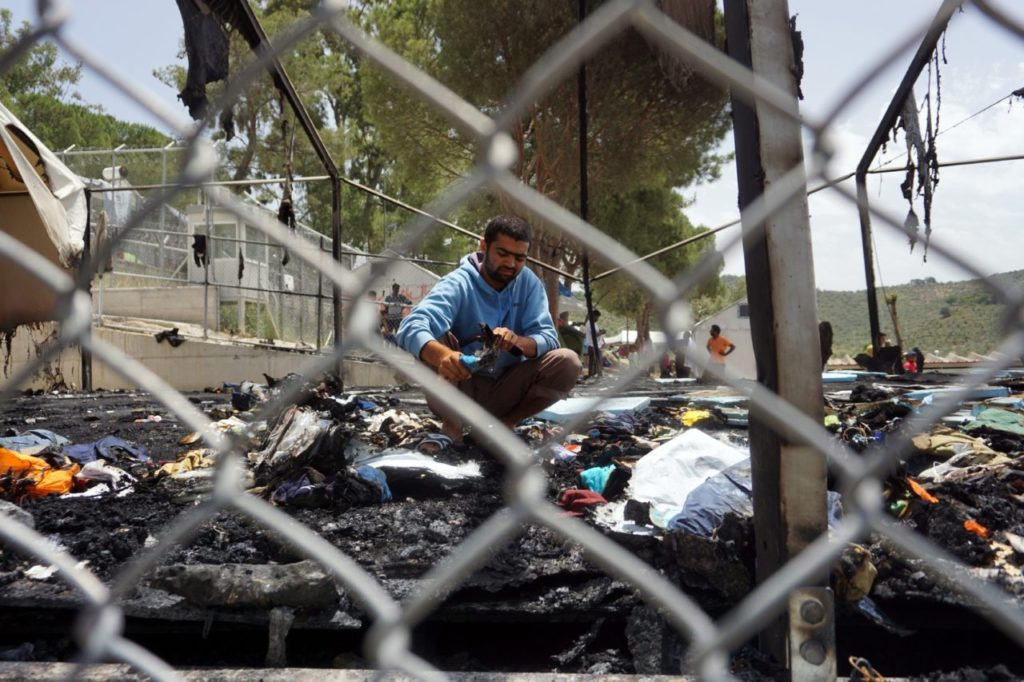 A migrant searches through the debris of a torched tent in the Moria detention camp on the Greek island of Lesbos, on June 2, 2016 following overnight clashes between Afghans and Pakistanis migrants. Over a dozen migrants were hurt on June 2 in a brawl in the main detention camp on Lesbos that also saw nearly 30 tents torched, an AFP correspondent said. / AFP / STR (Photo credit should read STR/AFP/Getty Images)