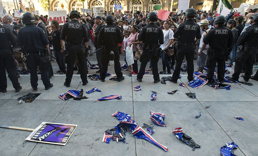 Torn Trump signs are seen on the ground behind a police skirmish line during a protest near where Republican presidential candidate Donald Trump held a rally in San Jose, California on June 02, 2016. Protesters attacked Trump supporters as they left the rally, burned an american flag, trump paraphernalia and scuffled with police and each other. / AFP / JOSH EDELSON (Photo credit should read JOSH EDELSON/AFP/Getty Images)