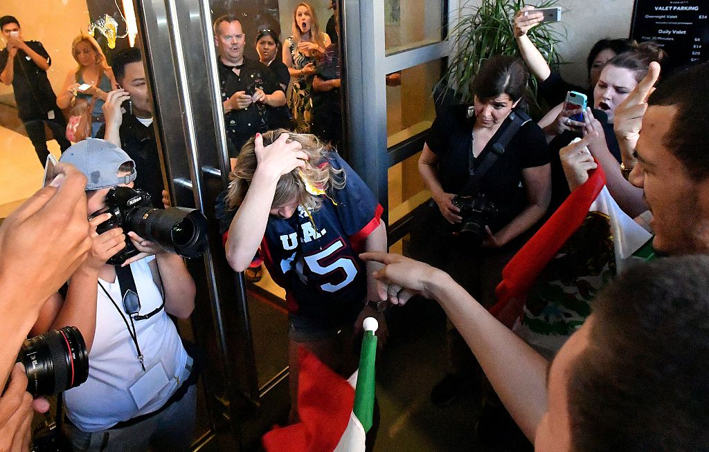 A woman wearing a Trump shirt (C) is pelted with eggs by protesters while pinned against a door near where Republican presidential candidate Donald Trump holds a rally in San Jose, California on June 02, 2016. Protesters attacked Trump supporters as they left the rally, burned an american flag, trump paraphernalia and scuffled with police and each other. / AFP / JOSH EDELSON (Photo credit should read JOSH EDELSON/AFP/Getty Images)