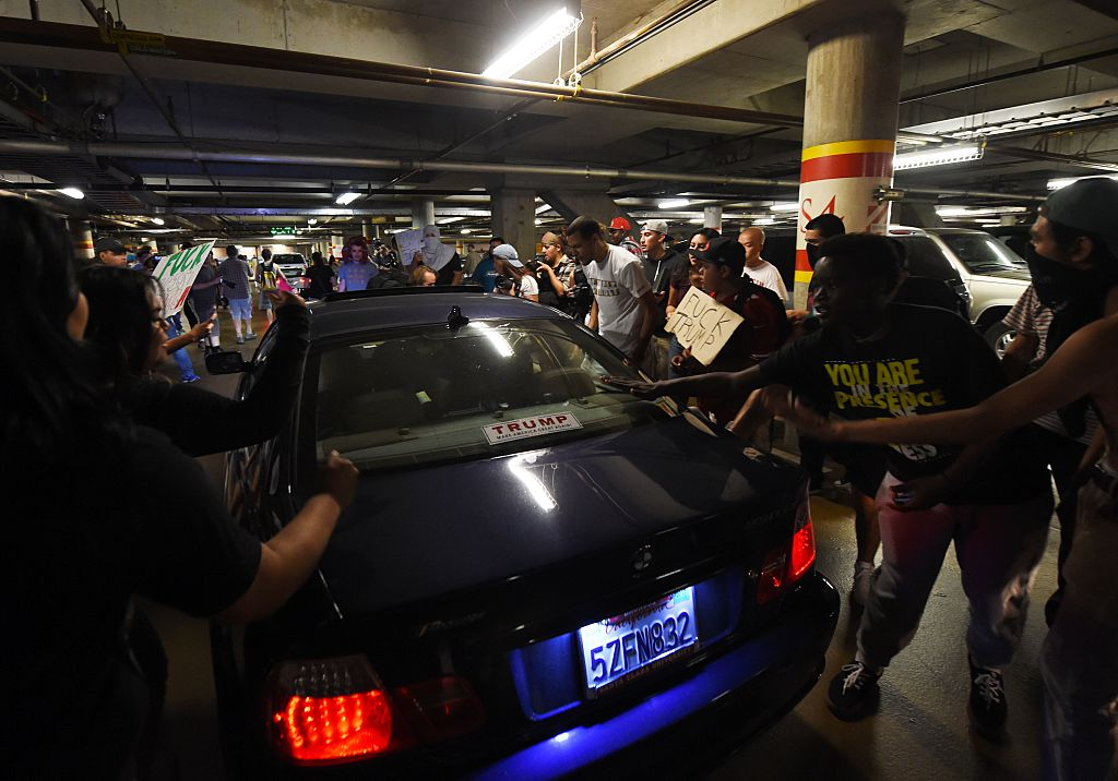 Anti-Trump protesters confront Trump supporters as they try to leave a parking garage at the convention center where Republican presidential candidate Donald Trump held an election rally in San Jose, California on June 2, 2016.  Protesters who oppose Donald Trump scuffled with his supporters on June 2 as the presumptive Republican presidential nominee held a rally in California, with fistfights erupting and one supporter hit with an egg. / AFP / Mark Ralston        (Photo credit should read MARK RALSTON/AFP/Getty Images)