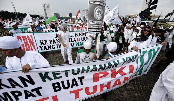 Hundreds of Islamic Defenders Front (FPI) members take part in a rally against communism in front of the presidential palace in Jakarta on June 3, 2016, to welcome in the holy month of Ramadan which begins on June 6. / AFP / BAY ISMOYO (Photo credit should read BAY ISMOYO/AFP/Getty Images)
