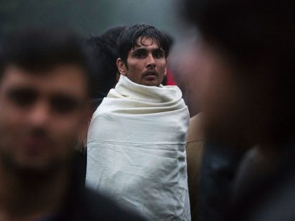 A migrant looks on as he wears a blanket on him during the evacuation of the Jardin d'Eole migrants camp, in Paris on June 6, 2016. The Jardin d'Eole, where more than a thousand people were installed for several weeks has been evacuated peacefully on June 6, 2016. / AFP …
