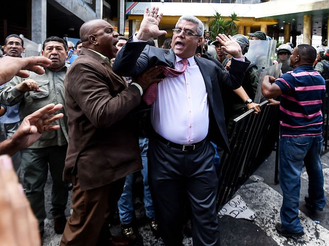 TOPSHOT - Supporters of Venezuelan president Nicolas Maduro argue with opposition deputy Alfonso Marquina(C) during a demonstration in front of the National Electoral Council in Caracas on June 9, 2016. / AFP / JUAN BARRETO (Photo credit should read JUAN BARRETO/AFP/Getty Images)