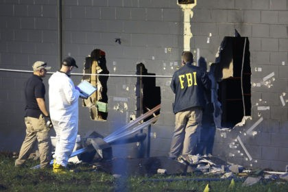 FBI agents investigate near the damaged rear wall of the Pulse Nightclub where Omar Mateen allegedly killed at least 50 people on June 12, 2016 in Orlando, Florida.