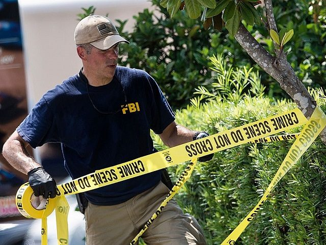A member of the FBI raises police tape near the Pulse nightclub June 13, 2016 in Orlando, Florida. Forty-nine people died and more than 50 were injured early June 12 when a heavily-armed gunman opened fire and seized hostages at a gay nightclub in Orlando, Florida, in the worst mass …