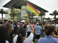 A woman holds a rainbow flag at a vigil for the victims of the Pulse nightclub shooting, on June 13, 2016 at the Dr. Phillips Center for the Performing Arts in Orlando, Florida.