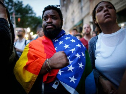 A man holds a flag during a vigil in solidarity for the victims killed at Pulse nightclub in Orlando in New York on June 13, 2016. The American gunman who launched a murderous assault on a gay nightclub in Orlando was radicalized by Islamist propaganda, officials said Monday, as they …