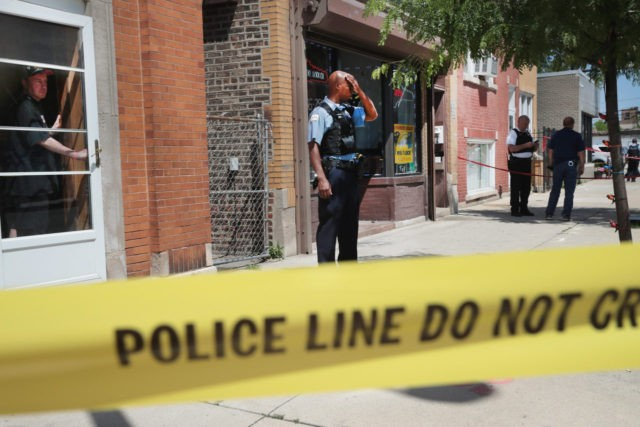 CHICAGO, IL - JUNE 15:  Police investigate a crime scene after two people were shot on the near Westside on June 15, 2016 in Chicago, Illinois. One witness said two area businessmen were arguing over the price of a service when one of the men pulled a gun and shot the other and his son after being assaulted with a baton.  One-thousand-six-hundred-eighty-nine people have been shot in Chicago since January 1.  (Photo by Scott Olson/Getty Images)