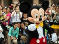 People take pictures of Mickey Mouse (in foreground) after the opening ceremony of the Shanghai Disney Resort in Shanghai on June 16, 2016.