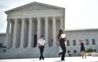 A reporter runs out of the US Supreme Court after the Court struck down a Texas law placing restrictions on abortion clinics, outside of the Supreme Court on June 27, 2016 in Washington, DC. In a case with far-reaching implications for millions of women across the United States, the court …