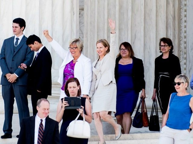 Texas abortion provider Amy Hagstrom-Miller and Nancy Northup, President of The Center for Reproductive Rights wave to supporters as they decend the steps of the United States Supreme Court on June 27, 2016 in Washington, DC.