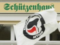 POESSNECK, GERMANY - MARCH 28: A protester waves a flag of the Antifa, or Antifaschistische Aktion ('anti-fascist action') as demostrators march past the 'Schuetzenhaus,' literally 'Clubhouse,' during an anti-Nazi rally on March 28, 2009 in Poessneck, Germany.