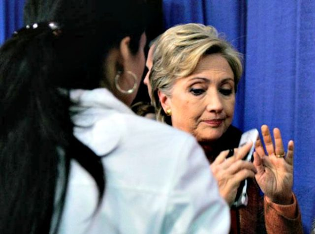 Hillary with a cell phone and Huma AP