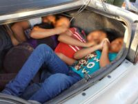 Human Smugglers pack people in trunk of car.