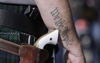 Man with Gun, We the People Tatoo AP PhotoEric Gay