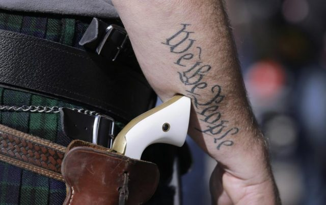 Man with Gun, We the People Tatoo AP PhotoEric Gay