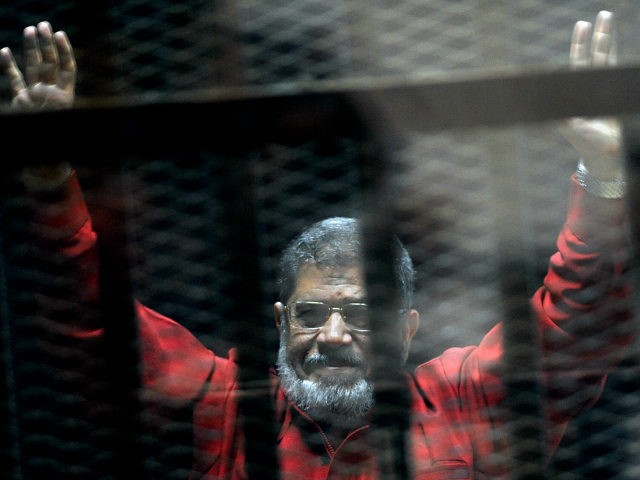 FILE - In this June 21, 2015 file photo, former Egyptian President Mohammed Morsi, wearing a red jumpsuit that designates he has been sentenced to death, raises his hands inside a defendants cage in a makeshift courtroom at the national police academy, in an eastern suburb of Cairo, Egypt. An …