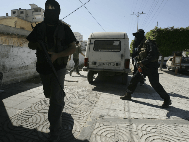 Members of the new security force of the Hamas-led government take cover during clashes with Palestinian security officers close to the Parliament building on May 22, 2006 in Gaza City, Gaza.