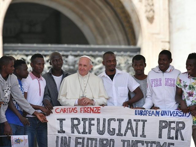 "Pope Francis poses surrounded by a group of refugees attending his weekly general audience at St Peter's square on June 22, 2016 in Vatican. The banner reads : ""For a Future all together"" / AFP / TIZIANA FABI (Photo credit should read TIZIANA FABI/AFP/Getty Images)"