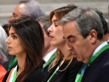 The new Mayor of Rome Virginia Raggi (L) and Italy's Minister for Constitutional Reforms and Relations with the Parliament Maria Elena Boschi (C) arrive at the Basilica of Saint John Lateran for the jubilee celebration mass on June 22, 2016 in Rome. / AFP / ALBERTO PIZZOLI (Photo credit should …