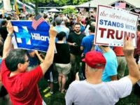 A supporter of Democratic presidential candidate Hillary Clinton and a Republican presidential candidate Donald Trump supporter hold signs as they attend a Memorial Day parade Monday, May 30, 2016, in Chappaqua, N.Y. Clinton and her husband former President Bill Clinton, along with New York Gov. Andrew Cuomo, walked in the parade. (AP Photo/Mel Evans)
