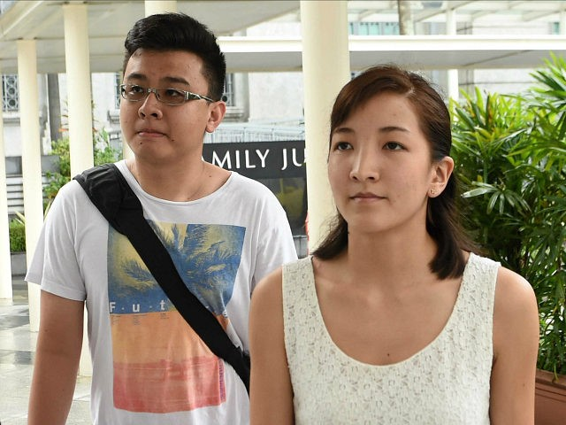Australian Japanese Ai Takagi (R), 23, and her Singaporean husband Yang Kaiheng (L), 27, arrives at the state court in Singapore on March 8, 2016. Takagi and Yang each face seven sedition charges for articles published between October 2013 and February 2015. / AFP / ROSLAN RAHMAN (Photo credit should …