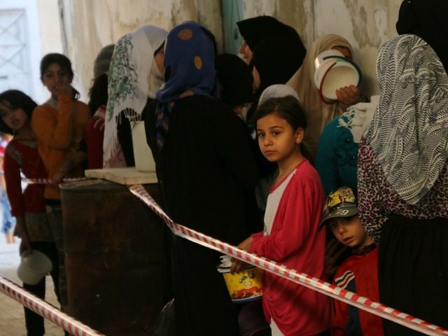 Syrians line-up waiting to receive meals distributed by the 'Syria charity' NGO to impoverished families during the Muslim holy fasting month of Ramadan on June 11, 2016 in a rebel-held neighbourhood of the northern city Aleppo.
