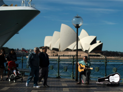 A man plays a song on a guitar on the Sydney Harbour in front of iconic Opera House on May 11, 2016. Australia's jobless rate was at 5.7 percent in March, but is forecast by the government in its annual national budget unveiled last week to fall to 5.5 percent …