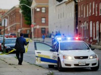 In this July 30, 2015 picture, a member of the Baltimore Police Department removes crime scene tape from a corner where a victim of a shooting was discovered in Baltimore. Murders are spiking again in Baltimore, three months after Freddie Gray's death in police custody sparked riots. This year's monthly …