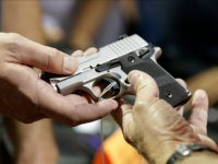 A gun seller shows a SIG Sauer hand gun to a customer at a gun show hosted by Florida Gun Shows, Saturday, Jan. 9, 2016, in Miami. Schlesinger purchased an Uzi and a Smith & Wesson 38. (AP Photo/Lynne Sladky)