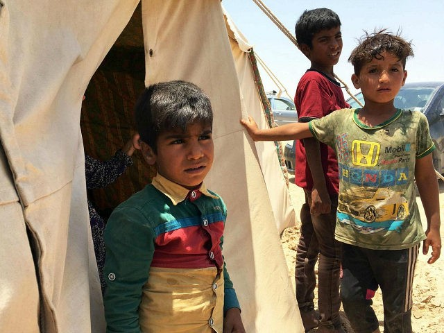 Iraq, Amriyat al-Fallujah : Displaced Iraqi boys stand on May 29, 2016 in front of a tent at a newly-opened camp in the government-held town of Amriyat al-Fallujah 50 kilometres (30 miles) southwest of Baghdad, which was set up to shelter people fleeing violence around the city of Fallujah. The Norwegian Refugee Council, which runs the camp in Amriyat al-Fallujah, says around 3,000 people have managed to flee the area and reach displacement camps since Iraqi forces launched an operation against the Islamic State a week ago. The biggest wave of arrivals so far was Saturday night and included mostly exhausted and hungry women and children. / AFP PHOTO / Jean Marc MOJON