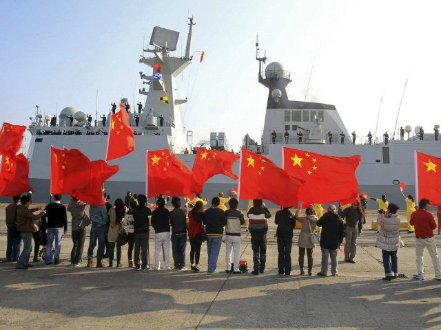 Chinese nationals living in Cyprus wave Chinese national flags as the Chinese frigate Yancheng comes in to dock at Limassol port, January 4, 2014. REUTERS/ANDREAS MANOLIS
