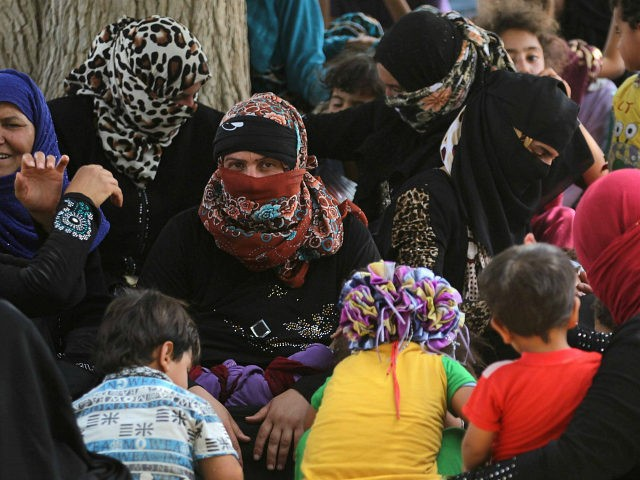 Displaced Iraqis, who fled the al-Falahat village west of Fallujah due to fighting between Iraqi government forces and the Islamic State (IS) group, wait to receive food and aid at the village of al-Azraqiyah, on June 4, 2016. Iraqi pro-government forces, made up of fighters from the army, the police and from the Hashed al-Shaabi, gained new ground from the Islamic State group in a key area west of the jihadist bastion of Fallujah, security sources said. / AFP / AHMAD AL-RUBAYE (Photo credit should read AHMAD AL-RUBAYE/AFP/Getty Images)