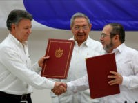 Colombian President Juan Manuel Santos, left, and Commander of the Revolutionary Armed Forces of Colombia or FARC, Timoleon Jimenez, right, shake hands during a signing ceremony of a cease-fire and rebel disarmament deal, in Havana, Cuba, Thursday, June 23, 2016. The deal moves Colombia closer to ending a 52-year war …