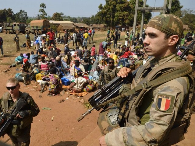French soldiers taking part in 'Operation Sangaris' stand guard as Muslim people wait to seek refuge at the Boali church, on January 19, 2014, in Boali, some 100km north of Bangui.