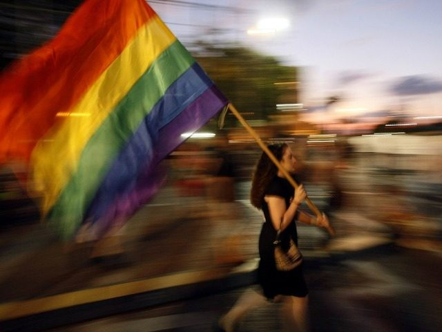 An Israeli woman waves a rainbow flag as she takes part in a demonstration of solidarity with the victims of an attack on a gay centre, in Tel Aviv's Rabin Square on August 8, 2009.