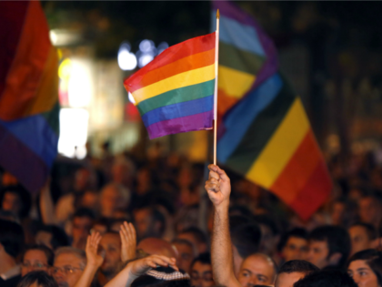 A man waves a rainbow flag as thousands of Israelis from the gay community and supporters gather in downtown Jerusalem on August 1, 2015 to protest against discrimination and violence against the gay community following an attack at the Jerusalem Gay Pride parade.