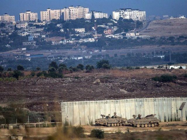"SDEROT, ISRAEL - JULY 18: Israeli tanks sit positioned next to a gap in the wall seperating Gaza and Israel on the morning July 18, 2014 near Sderot, Israel. Late last night the Israel operation ""Decisive Edge"" sent troops into Gaza, officially turning the offensive into a ground operation. (Photo …"