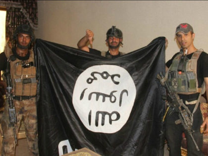 In this image taken by an Iraqi Counterterrorism Service photographer on Sunday, June 19, 2016, soldiers pose with an Islamic State militant flag in Fallujah, Iraq after forces re-took the city center after two years of IS control. Thousands of civilians are fleeing Fallujah after the city was declared liberated …