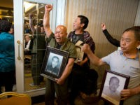 Ma Wenyi, center, holding a photo of his father who was forced to work during World War II at a mine for Mitsubishi Mining Corp., shouts as he demands to join a press conference in Beijing Wednesday, June 1, 2016. Mitsubishi Materials Corp., one of dozens of Japanese companies that used Chinese forced laborers during World War II, reached a settlement with thousands of victims on Wednesday that includes compensation and an apology. (AP Photo/Ng Han Guan)
