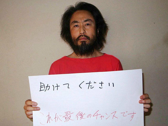 CORRECTION - This undated picture provided by Japan's Jiji Press news agency, taken at an undisclosed location, on May 30, 2016 shows Japanese freelance journalist Jumpei Yasuda holding a piece of paper with a handwritten message in Japanese. The fresh photo, which received widespread coverage in Japanese media on May …