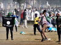 SRINAGAR, INDIA - SEPTEMBER 25: Kashmiri Muslim protesters throw stone as they carry a ISIS flag and portraits of local militants as tear gas shells exploded near them during the clashes between protesters and security men on September 25, 2015, in Srinagar, India. Kashmir valley witnessed restrictions with the government snapping internet services and placing separatist leaders under house arrest fearing anti-government protests over the decision of the Jammu & Kashmir High Court calling for implementing a ban on the sale of beef in the state and stopping of cow slaughter. Muslims on Eid al-Adha slaughter cattle, sheep and goats as a part of the Prophet Abrahamic tradition. (Photo by Abid Bhat/Hindustan Times via Getty Images)