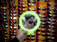 A Pakistani customer looks in a mirror as he shops for a pair of sun glasses at a vendor at the roadside in Islamabad, Pakistan, Wednesday, March 9, 2016. (AP Photo/B.K. Bangash)