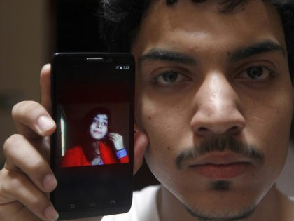 A Pakistan Hassan Khan shows the picture of his wife Zeenat Rafiq, who was burned alive by allegedly her mother, on a mobile phone at his home in Lahore, Pakistan Wednesday, June 8, 2016. A Pakistani woman was arrested Wednesday after dousing her daughter with kerosene and burning her alive, …