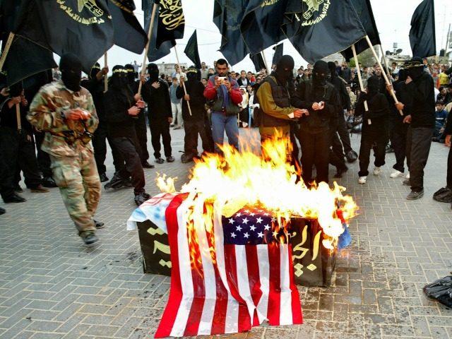Members of the Islamic militant group Jihad burn U.S, Israeli and British flags over a mock coffin symbolic of Arab armies during an anti-American, British and Israeli rally April 11, 2003 at the Jabalia refugee camp, Gaza Strip.