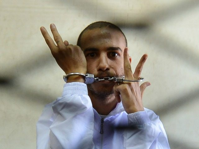 Egyptian Copt Albert Saber, 27, flashes the V for 'victory' sign from inside the holding cage during the opening session of his trial in Cairo on September 26, 2012, on charges of blasphemy, insulting religions and inciting sectarianism through his Internet postings.