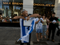 An Israeli man hungs an Israeli flag outside Max Brenner restaurant in Sarona Market on June 9, 2016 in Tel Aviv, Israel. According to police reports, four Israelis were killed and several others wounded when two Palestinian gunmen open fire at the food and retail complex in central Tel Aviv.
