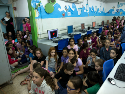 Israeli schoolchildren gather in a bomb shelter at a school in Jerusalem after sirens sounded across Israel as part of country-wide massive civil defence exercise aimed at preparing the country for air or missile attacks involving non-conventional weapons on June 2, 2015. AFP PHOTO / MENAHEM KAHANA (Photo credit should …