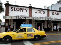KEY WEST, FL - SEPTEMBER 12: A taxi drives past Sloppy Joe's Bar on Duval Street on September 12, 2013 in Key West, Florida. The city recently enacted a Key West City Ordinance that will allow taxi cab drivers to charge $50 over the price of the cab ride to an intoxicated person who vomits in a cab. The fine would be levied against an intoxicated passenger but not children or sober riders who become ill. (Photo by Joe Raedle/Getty Images)