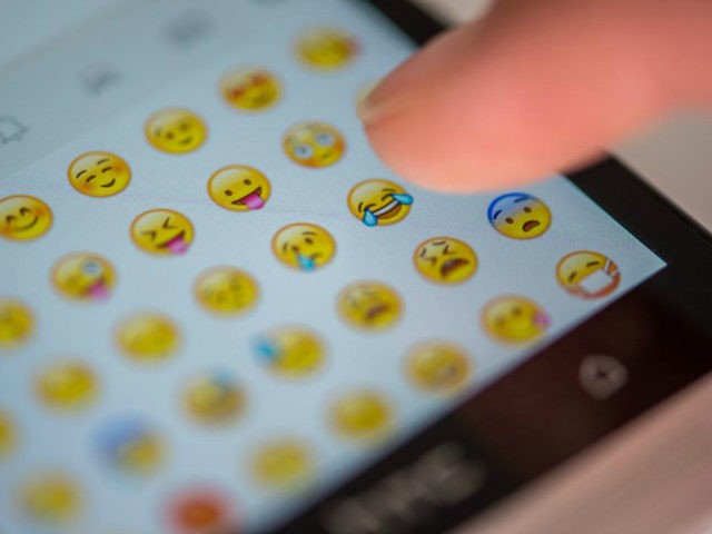 """ILLUSTRATION - Eine Frau tippt am 24.08.2015 in München (Bayern) auf das Display eines Smartphones, auf dem zahlreiche Emojis in der Nachrichten-App """"Whatsapp"""" zu sehen sind. Photo by: Matthias Balk/picture-alliance/dpa/AP Images"""